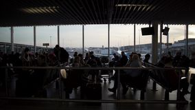 Tourists waiting for boarding at departure lounge, people sitting in airport. Stock footage stock footage