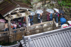 Tourists waiting in line to drink holy water from waterfall Royalty Free Stock Image
