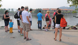 Tourists waiting at the pier for boarding to the fishing boats Stock Photos