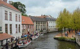 Tourists waiting in queue for boat tour on Bruges canal royalty free stock image