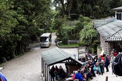 Tourists Waiting To Enter Inca Ruins At Machu Picchu Peru South. Machu Picchu, Peru - June 20, 2015: Tourist Waiting To Enter Inca Ruins With Signs, Bus, Trees stock photos