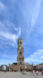 Tourists walinkg in front of the Belfry Tower in the market square in the center of Bruges, a beautiful medieval town in Belgium Royalty Free Stock Images