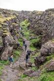 Tourists walk through the Almannagja fault line in the mid-atlantic ridge north american plate in Thingvellir National Park. Icela. Thingvellir, Iceland - July royalty free stock photos