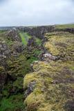 Tourists walk through the Almannagja fault line in the mid-atlantic ridge north american plate in Thingvellir National Park. Iceland stock photo