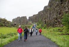 Tourists walk through the Almannagja fault line in the mid-atlantic ridge north american plate in Thingvellir National Park. Thingvellir, Iceland - July 19, 2017 stock images