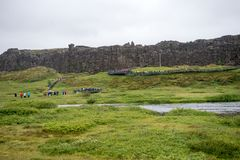 Tourists walk through the Almannagja fault line in the mid-atlantic ridge north american plate in Thingvellir National Park. Thingvellir, Iceland - July 19, 2017 stock photography