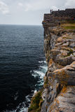Tourists walk along edge of cliffs on Inishmore Island Royalty Free Stock Photography