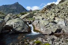 Tourists walk along a key in a mountain valley Barguzinsky ridge Royalty Free Stock Photos