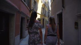 Tourists walk along narrow Italian street enjoying travel