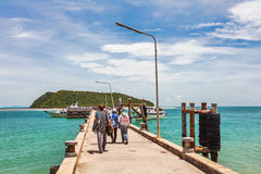 Tourists walk along the pier to the boat Royalty Free Stock Image