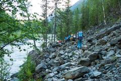 Tourists walk along the river Akkem. Trekking in the Altai Mountains Royalty Free Stock Photo