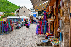 Tourists walk along a street full of shops, in the historic center of Mostar, Bosnia and Herzegovina Stock Photos