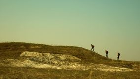 Tourists walk along the top of the hill. joint work of business people. The team of travelers goes to victory and. Tourists walk along the top of hill. joint stock photos