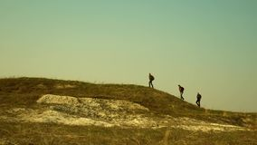 Tourists walk along the top of the hill. joint work of business people. The team of travelers goes to victory and. Tourists walk along the top of hill. joint royalty free stock images