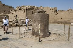Tourists walk around the red granite statue of a sacred scarab at the Temple of Karnak in Luxor in Egypt. Stock Images