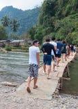 Tourists walk on the bridge. Vang Vieng. Laos. Royalty Free Stock Photos