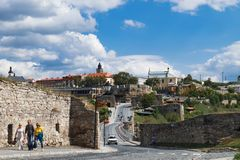 Tourists walk and enjoy Kamianets-Podilskyi Castle. Kamianets-Podilskyi, Ukraine - September 5, 2017: Tourists walk and enjoy old cobbled streets of historical royalty free stock photos