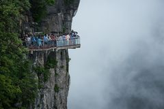 Tourists walk the famous see through glass walkway in Tianmen Mountain. Zhangjiiajie holds another beautiful mountainous secret in the Avatar karst peaks as the royalty free stock images