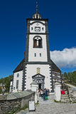 Tourists walk in front of the Roros church and bell tower in Roros, Norway. Stock Photo