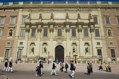 Tourists walk in front of the Royal palace building in Stockholm, Sweden. Stock Photo