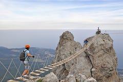 Tourists walk along a suspension bridge between rocks in Yalta. Tourists walk on the hanging bridge between rocks in Yalta, Russia stock image