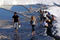 Tourists walk through the man-made pools at Cotton Castle at Pamukkale in Turkey. Royalty Free Stock Image