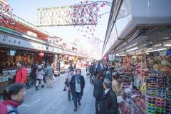 Tourists walk on Nakamise Dori in Sensoji shrine. The Nakamise Dori is a street with food and souvenirs shops in Senso-ji shrine, Stock Photo