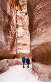 Tourists walk in narrow Siq passage to Petra town Stock Images