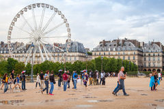 Tourists walk near Louvre on Tuileries park with Ferris wheel Royalty Free Stock Photo
