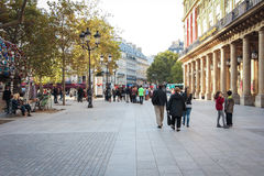 Tourists walk past a coffee shop and souvenir store in Paris. Stock Image