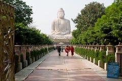 Tourists walk past 24.38 metre Buddha statue Stock Photo