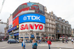 Tourists walk by Piccadilly Circus in London Royalty Free Stock Image