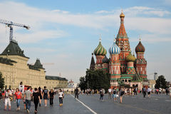 Tourists walk on the Red Square in Moscow. MOSCOW - JULY 16, 2016: Tourists walk on the Red Square in Moscow. Saint Basil Cathedral. UNESCO World Heritage Site royalty free stock photography