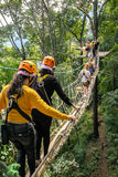 Tourists walk on the rope bridge walkway through the treetops in Stock Photography