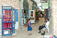 Tourists walk by shops and art galleries in Safed. S old city alleys Royalty Free Stock Image