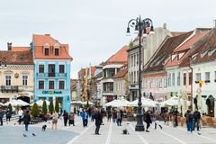 Tourists walk in the Square of Council Market around the Historical Museum and see the sights in the Old Town of Brasov in Romania Stock Photography