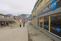 Tourists walk by the street of Longyearbyen, Norway. stock photography