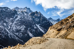 Tourists walk to black mountain with snow on the top and yellow stone ground at Thangu and Chopta valley in winter in Lachen. North Sikkim, India Stock Photo