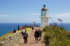 Tourists walk toward lighthouse at Cape Reinga, Northland, New Zealand Royalty Free Stock Image