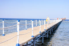 Tourists walking across a wooden pier. Crossing shallow tidal water towards distant wooden buildings at the end in deep water Stock Photos