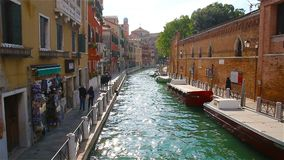 Tourists are walking along the canal in Venice, Italy stock video