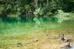 Tourists walking along a hiking path across the lake. Small figures of tourists walking along a hiking path across the lake with emerald transparent water Stock Photography