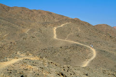 Tourists walking along a mountain path. Egypt, Sinai Peninsula, Taba royalty free stock photography