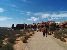 Tourists walking along path at Arches National Park. Toward rock formations, with sand a bushes on the sides Stock Photo