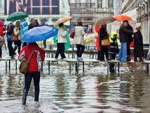 Tourists walking along raised walkways in Venice. Venice Italy, 16 Nov 2011: Lady with blue umbrella walking towards raised walkways during Acqua Alta flooding Stock Images