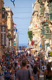A tourists walking along the Republic street of Valletta, Malta. Valletta, MALTA - JULY 24, 2015: A tourist crowd walking along the Republic street of Valletta Stock Photo