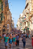 A tourists walking along the Republic street of Valletta, Malta. Valletta, MALTA - JULY 24, 2015: A tourist crowd walking along the Republic street of Valletta Royalty Free Stock Image