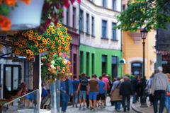 Tourists walking along the street of the old town with flowers i Royalty Free Stock Photos