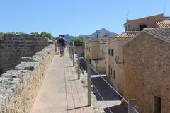 Tourists walk on the ancient city walls in Alcudia, Mallorca, Spain Stock Image