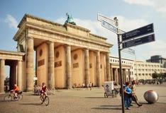 Tourists walking around famous historical Brandenburg gate Stock Photos